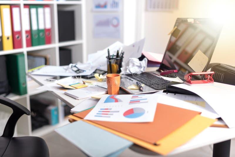 Upaćkany i cluttered biurko, lekki skutek zdjęcie stock
