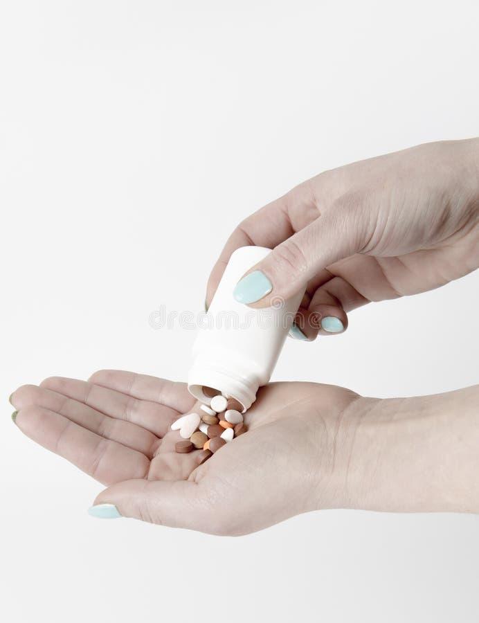 Upadek pastylki od białej lekarstwo butelki w ludzką rękę fotografia stock