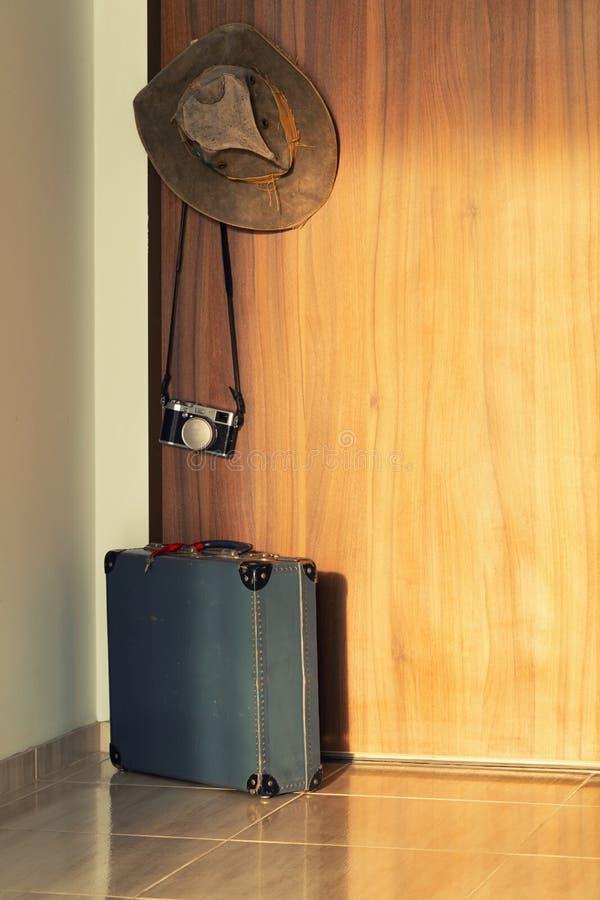 Upakowana walizka z kamery pozycją przed drzwi, rocznika styl pojęcie wakacyjna wycieczka obraz royalty free