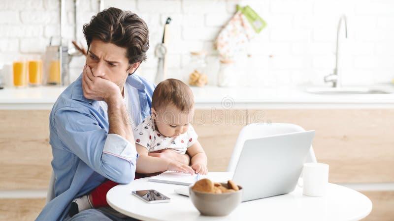 Uparty mężczyzna siedzący z synem w kuchni, nie może pracować zdjęcia stock