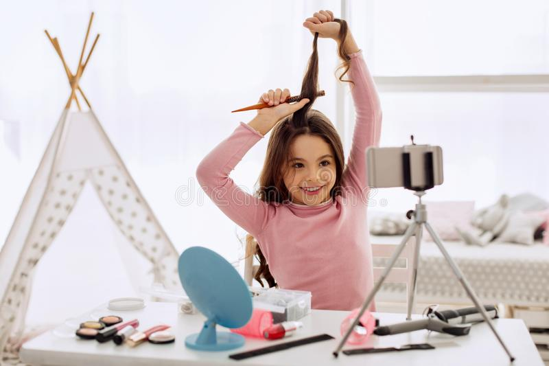 Upbeat girl filming hairstyle tutorial and smiling. Successful teenage blogger. Happy pre-teen girl brushing a lock of hair and smiling cheerfully at the camera royalty free stock photo