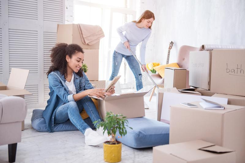 Upbeat girl looking at photo while her roommate cleaning floor stock images