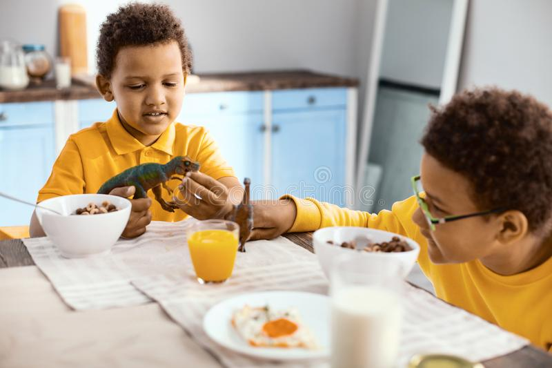 Upbeat little boys playing with toy dinosaurs in kitchen royalty free stock image