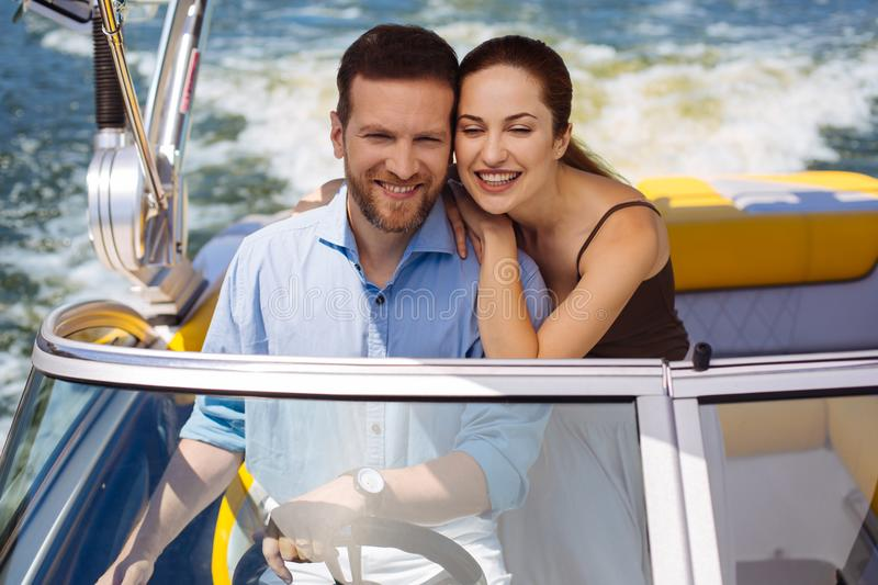 Upbeat young couple having maiden voyage on yacht stock images