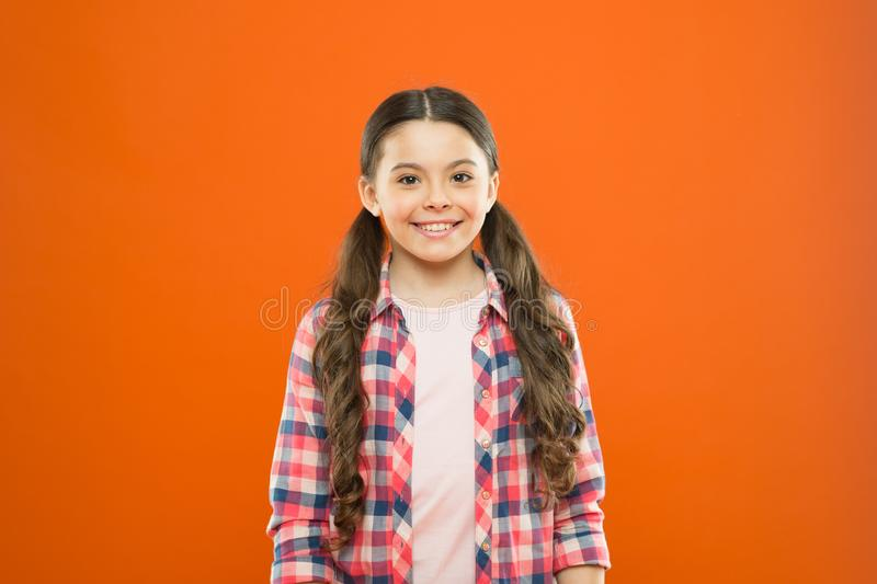 Upbringing versatile personality. Wellbeing and health. Childhood concept. Girl child stand orange background. Happy. Childhood. Grow mentally and physically stock photography