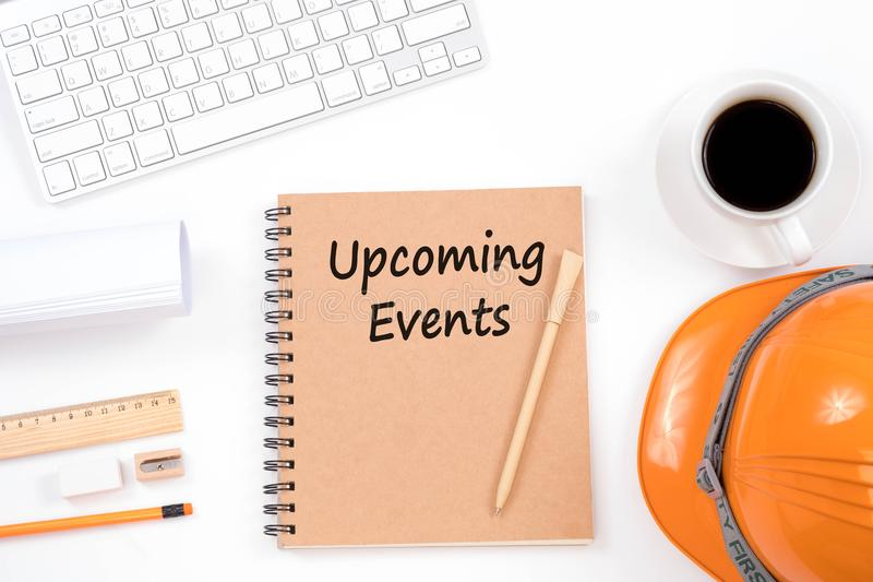 Upcoming Events concept. Top viwe of modern workplace with safety helmet, office supplies, a cup of coffee and keyboard on white royalty free stock images