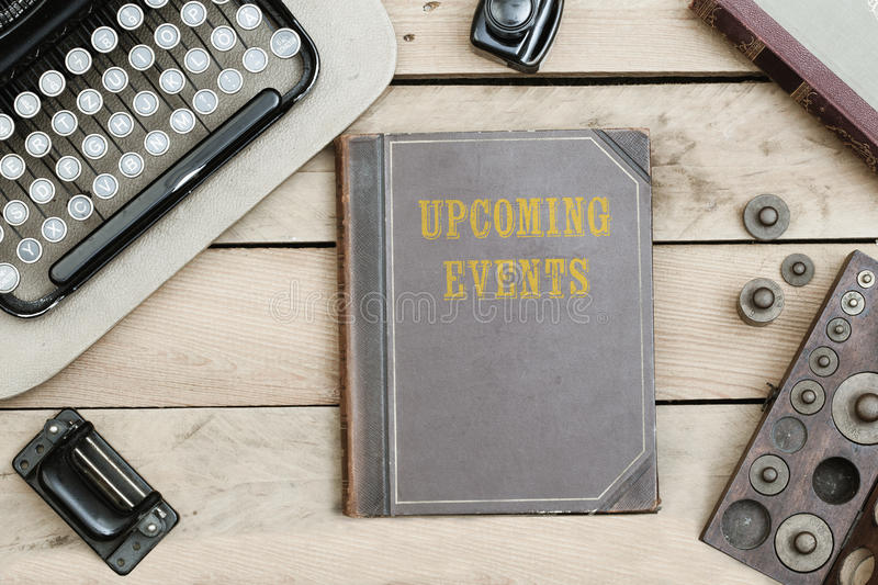 Upcoming Events on old book cover at office desk with vintage it stock photo