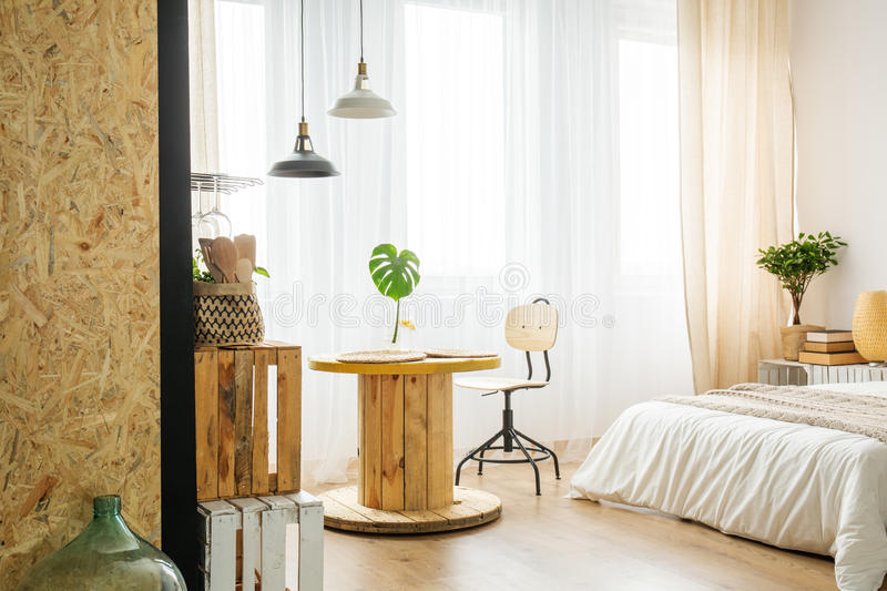 Upcycled table from cable spool in bedroom royalty free stock images