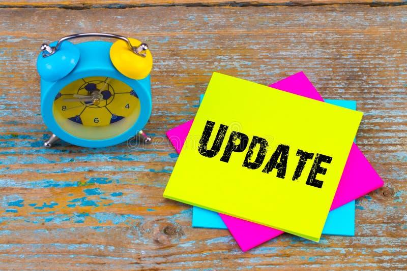 Update - op kleverige nota met wekker op houten achtergrond stock foto's