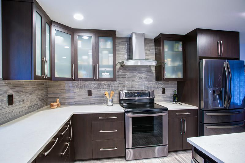 Updated contemporary kitchen room interior in white and dark tones. royalty free stock photography