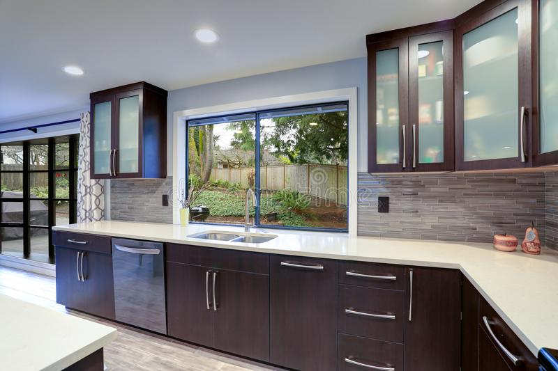 Updated contemporary kitchen room interior in white and dark tones. royalty free stock photo