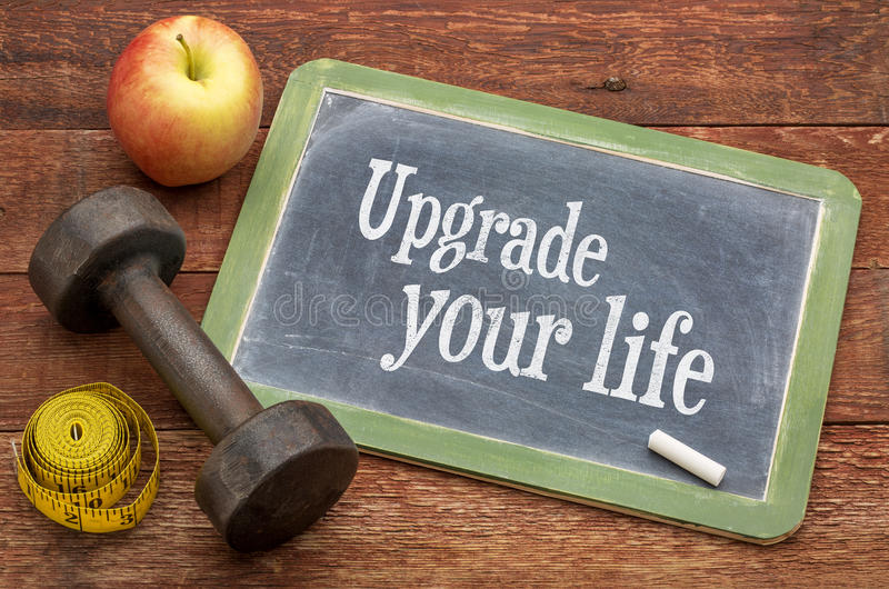 Upgrade your life concept. Text on slate blackboard against weathered red painted barn wood with a dumbbell, apple and tape measure stock photo