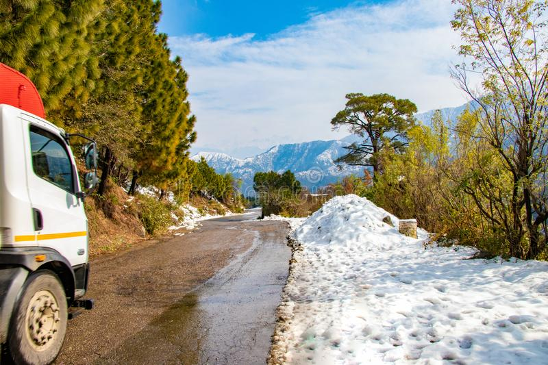 Uphill road in winter at banikhet dalhousie himachal pradesh india with sideways full of snow stock photos