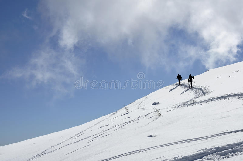 Uphill with snow shoes, dolomites. View of snowy slope in dolomite with people going uphill with snow-shoes, shot in bright winter light with some puffy clouds stock images