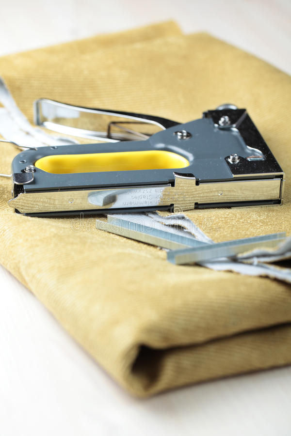 Upholstery stapler. On a piece of fabric royalty free stock images