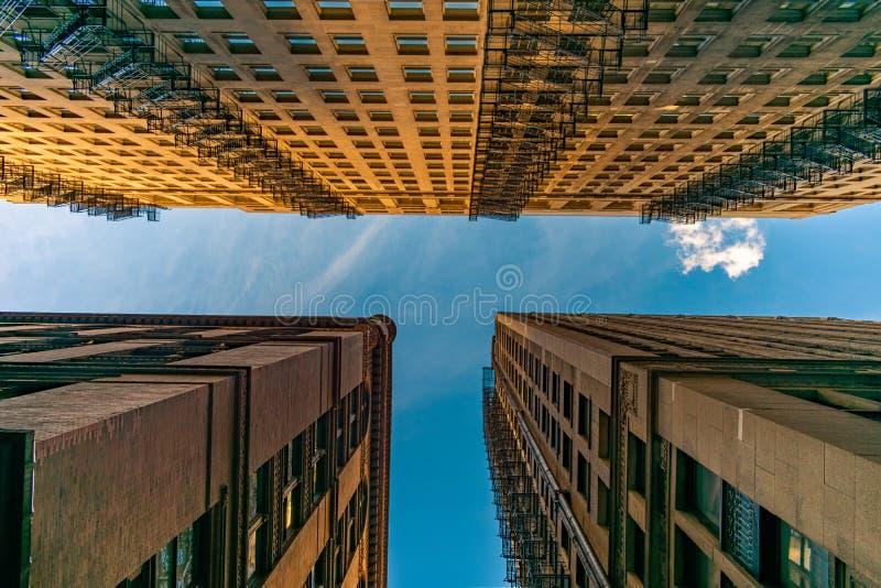 Uppåtriktad sikt av gamla stadsskyskrapor med brandflykter arkivfoto