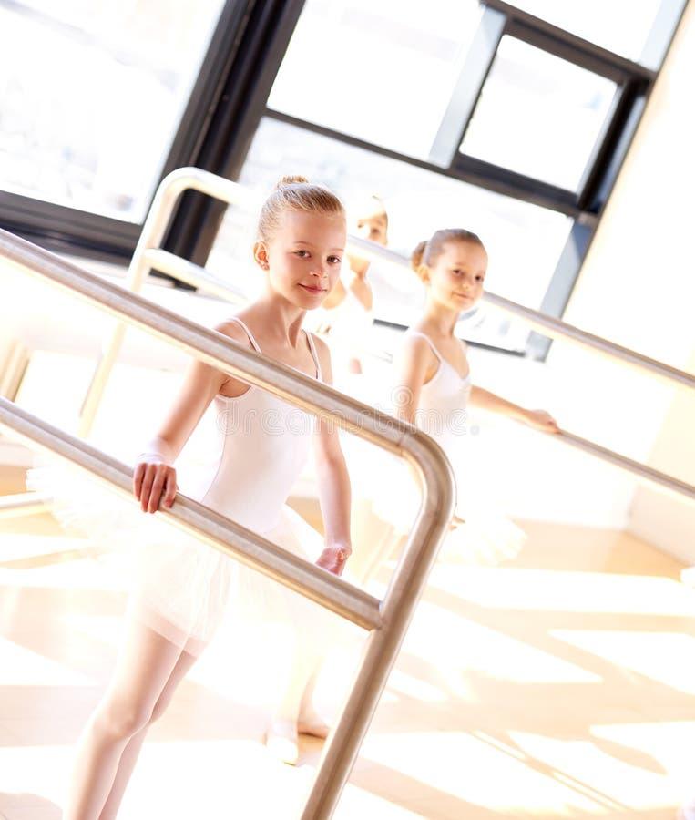 Uppåtsträvande unga ballerina som öva på stången royaltyfria bilder