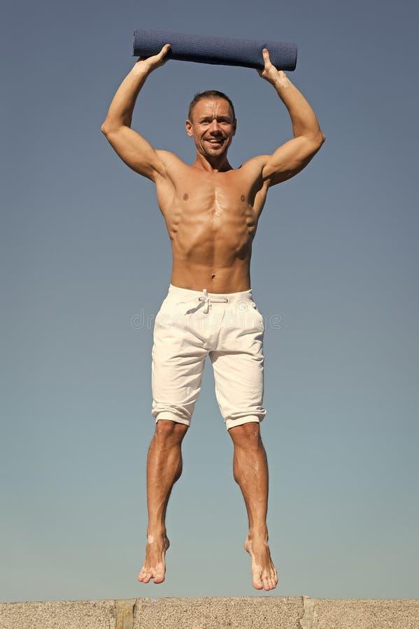 Upp till sund livsstil Man med mattt f?r yoga som f?ngas i himmelbakgrund f?r mitt- luft Idrottsman med mattt hopp utomhus- utbil arkivfoton