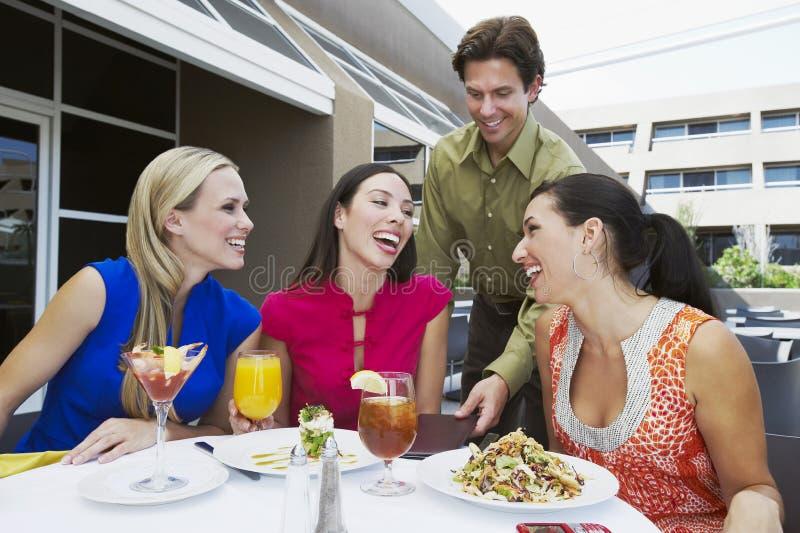 Uppassare Bringing Check till kvinnor i restaurang arkivfoto