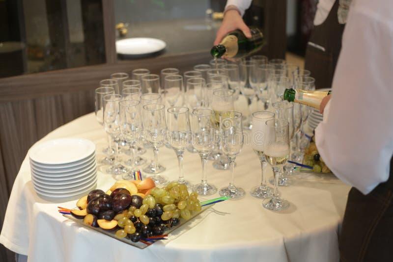 Uppassare häller champagne i exponeringsglas, druvor, skivor av äpplen och plommoner på tabellen royaltyfri fotografi