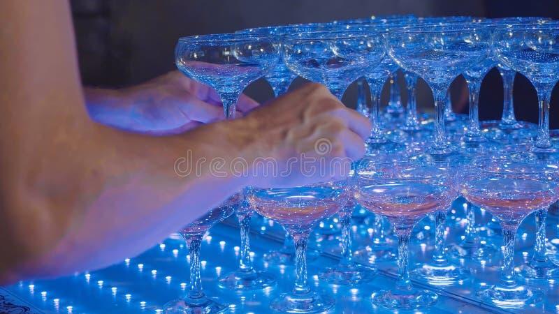Uppassare som gör en pyramid av champagneexponeringsglas, närbild arkivbilder