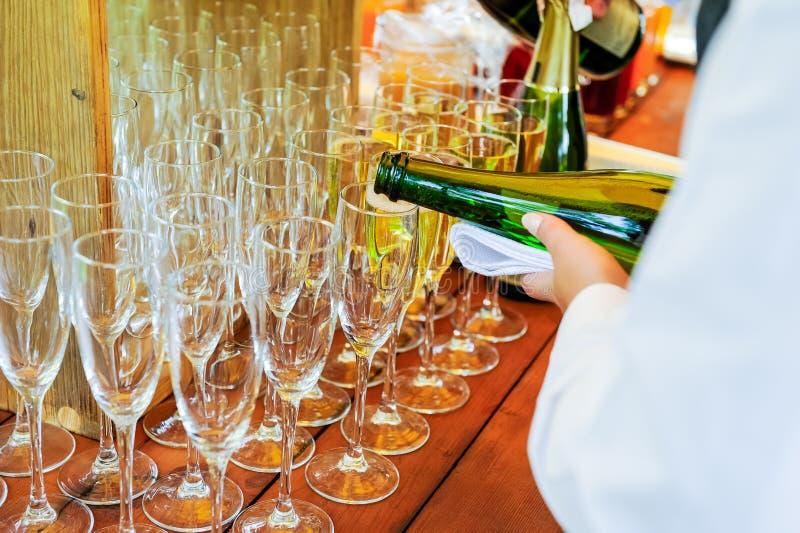 Uppassare som häller personlig portionChampagne i exponeringsglas Sköta om service på händelser, företags möte, parti, bröllop Se royaltyfria foton