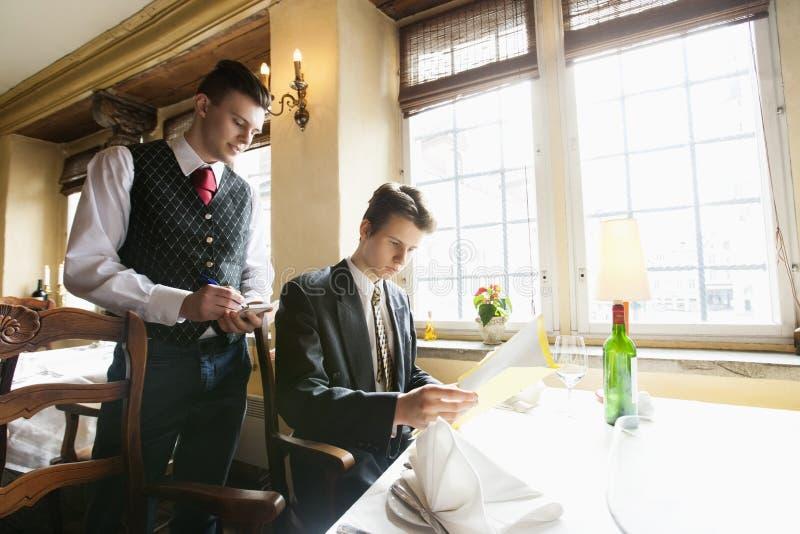 Uppassare som tar affärsmans beställning på restaurangen arkivbild