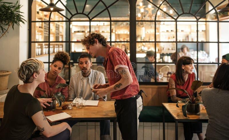 Uppassare som tar beställningar från kunder som sitter i en bistro royaltyfri foto