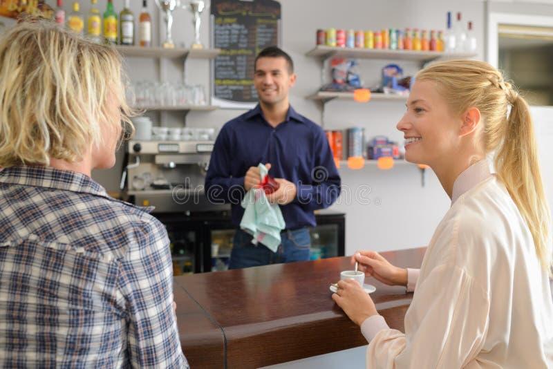 Uppassare som väntar för att ta beställning från två kvinnor i kafé royaltyfri bild