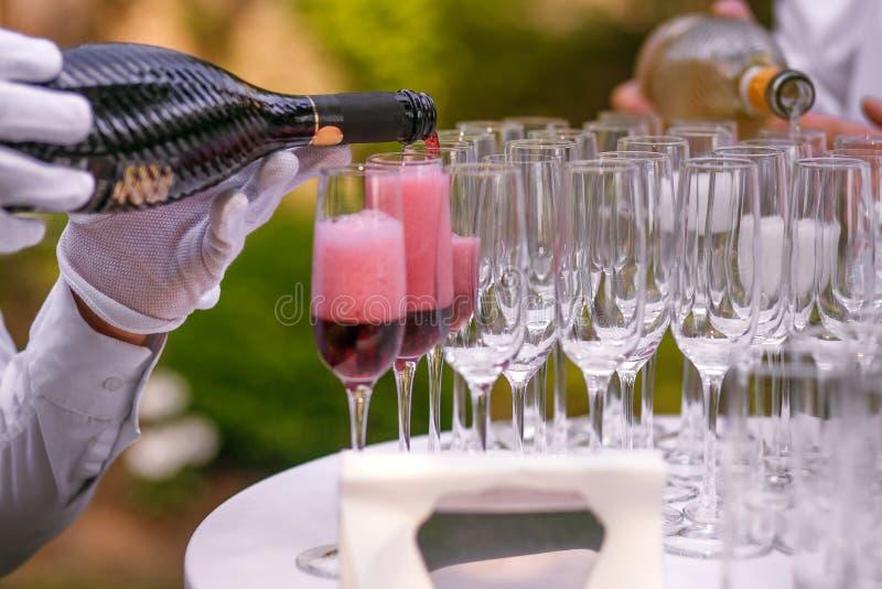 Uppassaren häller champagne in i exponeringsglas för ett parti, rött vin i exponeringsglas, champagne på en beröm arkivbilder