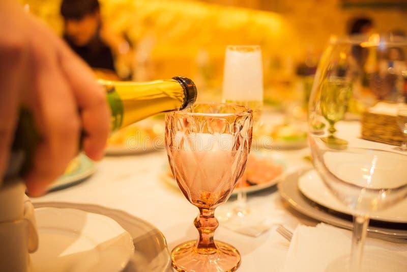 Uppassaren häller champagnen in i exponeringsglaset arkivbilder