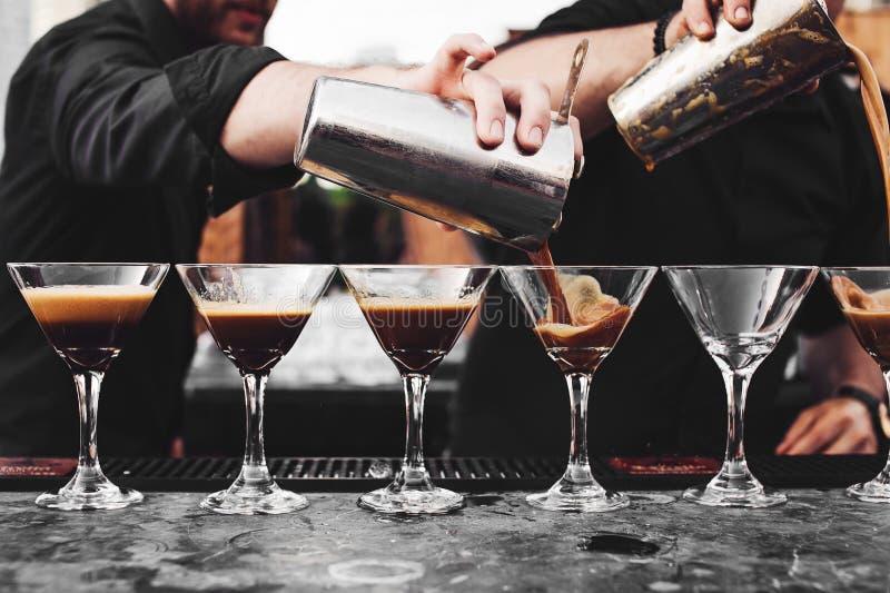 Uppassaren häller vin in i ett exponeringsglas royaltyfri foto