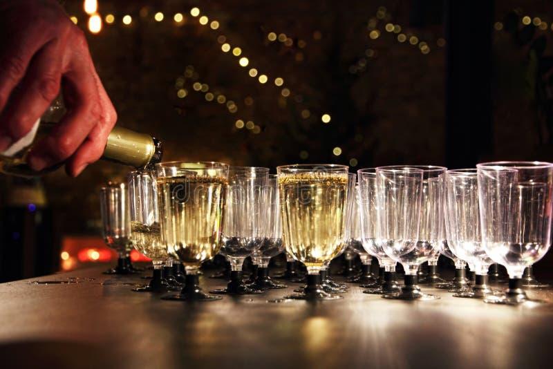 Uppassaren häller vin i exponeringsglaset på feriemottagandetabellen royaltyfri fotografi