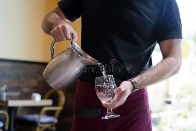 Uppassaren i restaurangen häller vattnet från tillbringaren in i exponeringsglaset royaltyfria foton