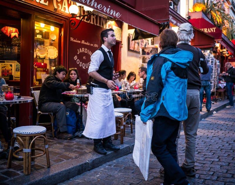 Uppassaren inviterar par in i hans restaurang på Montmartre i Paris arkivfoton