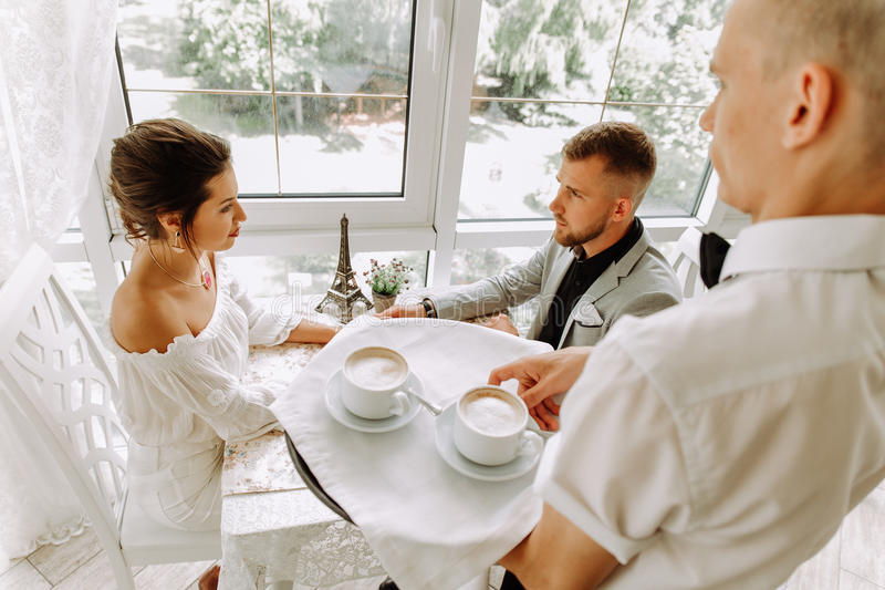 Uppassaren kom med koppen kaffe för härliga par i ett kafé royaltyfri foto