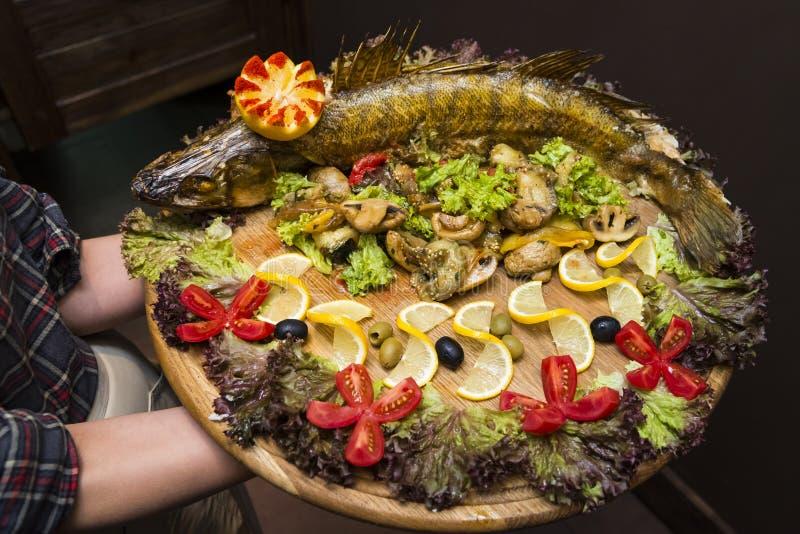 Uppassaren rymmer en stor planka med en stor aptitretande bakad fisk royaltyfri fotografi