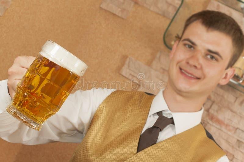 Uppassaren rymmer exponeringsglas av öl fotografering för bildbyråer
