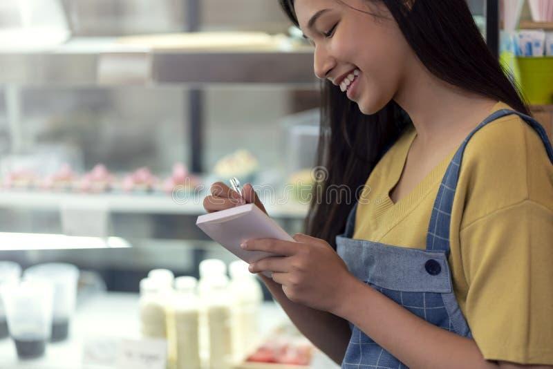 Uppassaren som skriver en beställning in i en anteckningsbok på bakelsekakan, shoppar, des royaltyfria foton