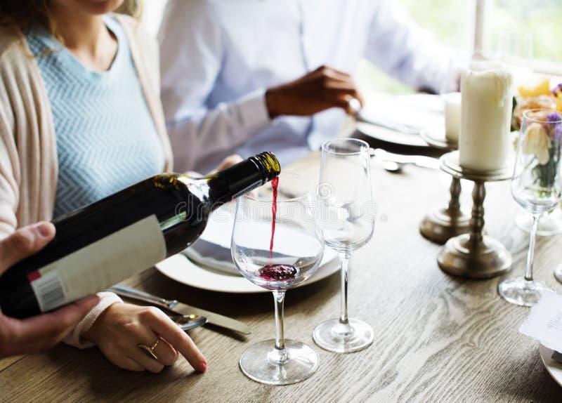 UppassarePoring Serving Red vin till kunder i en restaurang arkivbilder