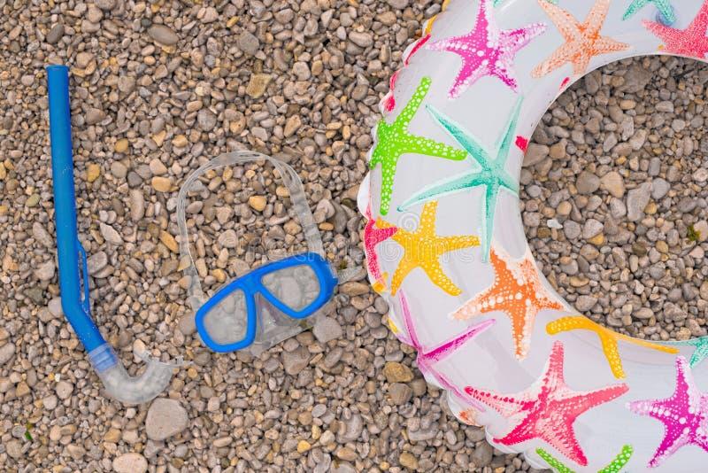 Uppblåsbar behandla som ett barn snorkeln för maskeringen för cirkelsandaler den undervattens-, lögn på t royaltyfri foto