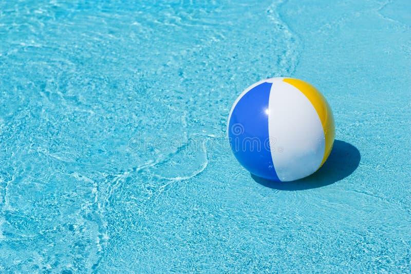 Uppblåsbar strandboll som svävar på kanten av pölen arkivbilder
