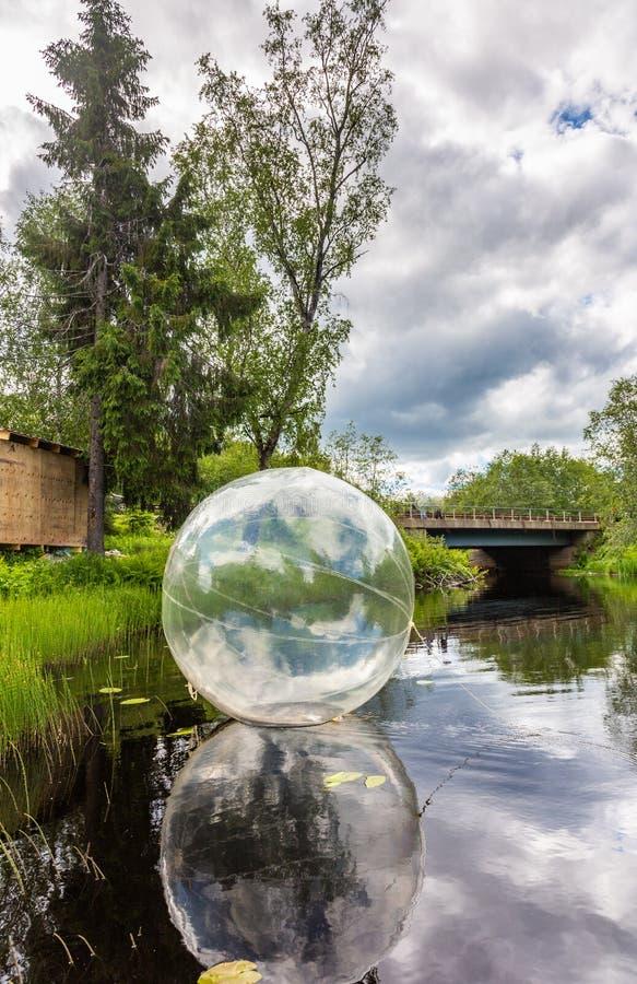 Uppblåsbara genomskinliga flöten för en boll på yttersidan av en behållare på de Ruskeala vattenfallen i en skog under en blå him royaltyfri foto