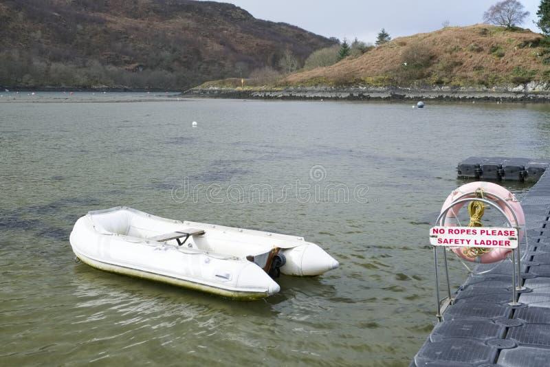 Uppblåsbart fartyg för jolle på pontonbryggan i den Crinan hamnen Skottland royaltyfria bilder