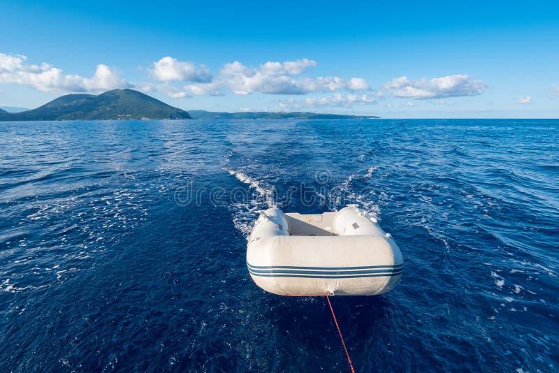 Uppblåsbart litet fartyg för jolle som (eller dingey) bogseras av en yacht i royaltyfri fotografi