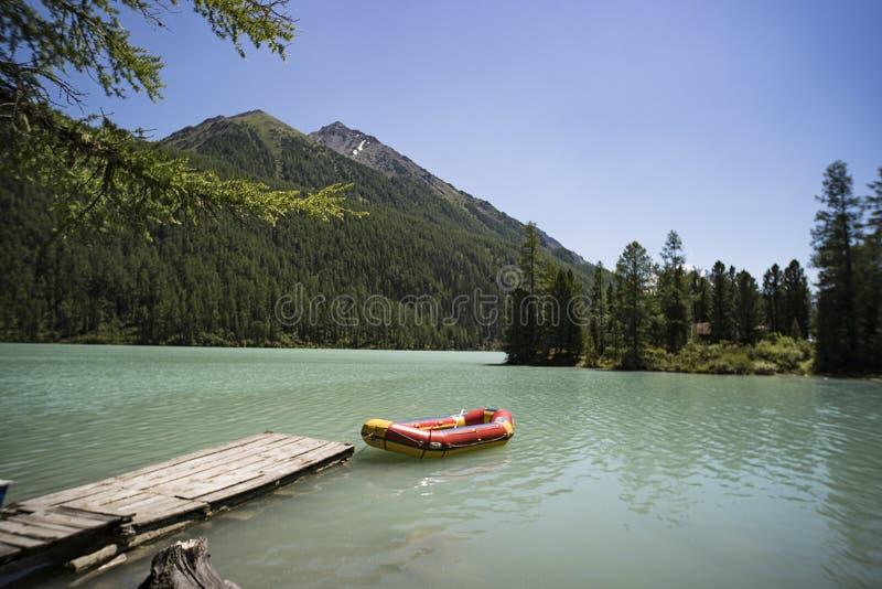 uppblåsbart rött fartyg i belterwiedesjön Rött fartyg på träbron i den blåa sjön Sibirien Altai vildmark Ryssland fis arkivfoton