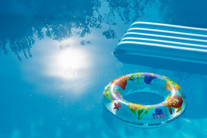Uppblåst boj och madrass som svävar på vatten av en simbassäng Sommar och feriebegrepp med ciopy utrymme arkivfoto