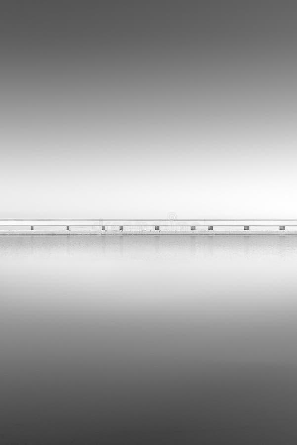 Uppdelning mellan en sjö och himlen, till och med en bro arkivfoto