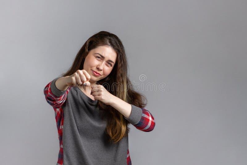 Uppehåll En ung kvinna med ett missnöjt ansikte visar aggressivt sina fister Kopiera utrymme arkivfoto