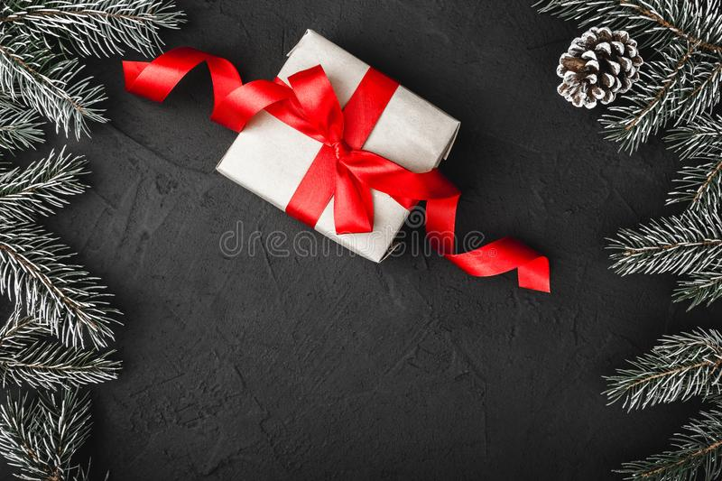 Upper, above, top view of pine, evergreen, and Christmas present with red ribbon on stone background. Upper, above, top view of pine, evergreen, and Christmas stock photo